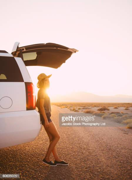 Hispanic woman leaning on car on remote road