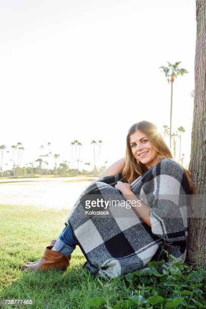 Hispanic woman leaning on tree