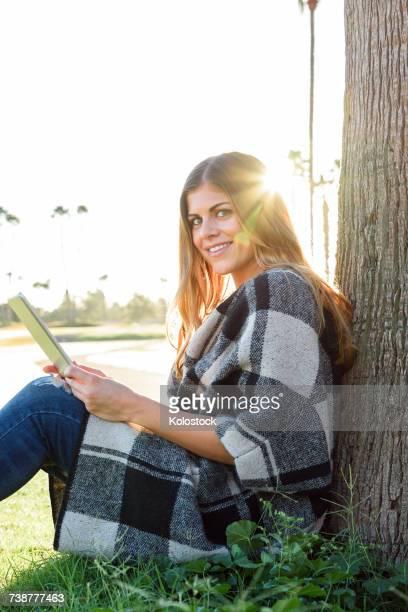 Hispanic woman leaning on tree using digital tablet