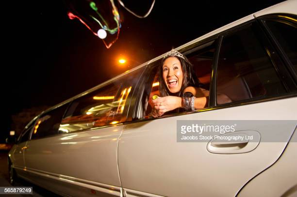 Hispanic woman leaning out limousine window at night