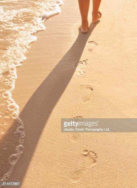 Hispanic woman leaving footprints on tropical beach