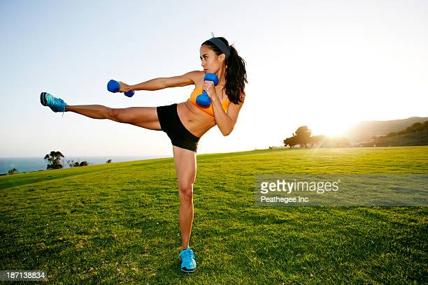 Hispanic woman lifting weights in field