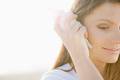 Hispanic woman listening to seashell