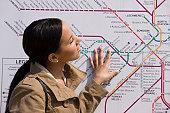 Hispanic woman looking at a route map at a subway station