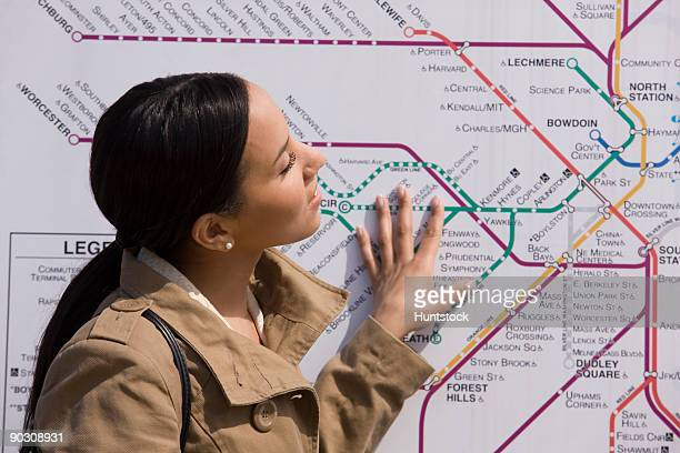 Hispanic woman looking at a route map at a subway station