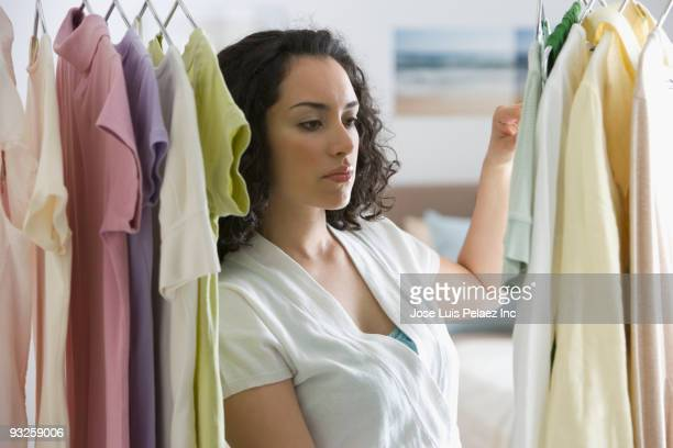 Hispanic woman looking at clothing in closet