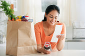 Hispanic woman looking at grocery receipt