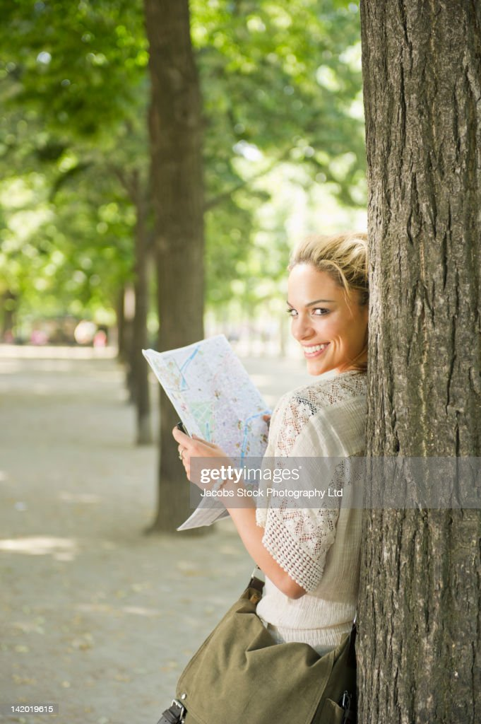 Hispanic woman looking at map in park : Stock Photo