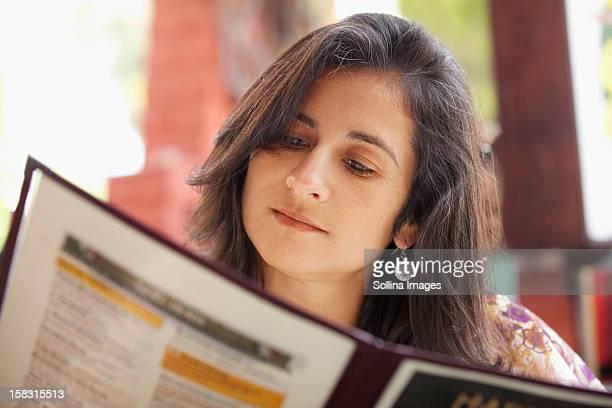 Hispanic woman looking at restaurant menu