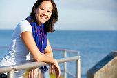 Hispanic Woman Looking Over Railing At Sea Smiling To Camera Wearing Scarf