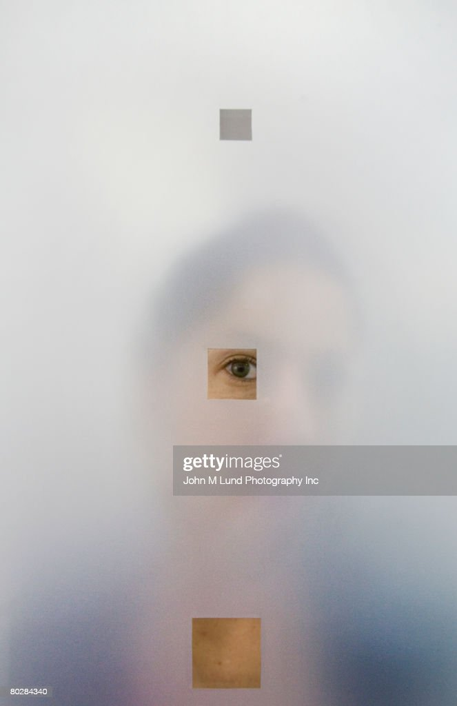Hispanic woman looking though hole in frosted glass : Stock Photo