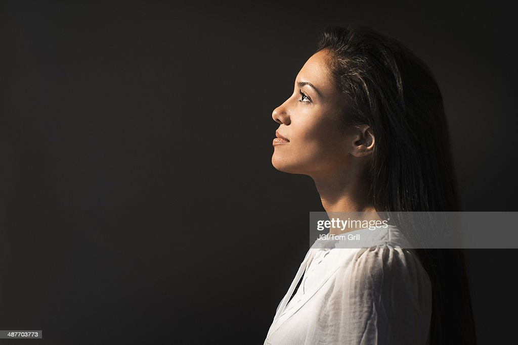 Hispanic woman looking up into light : Stock Photo