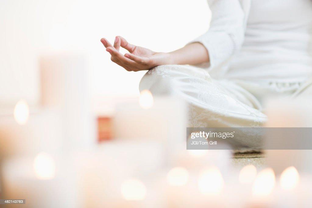 Hispanic woman meditating in lotus position near lit candles : Stock Photo