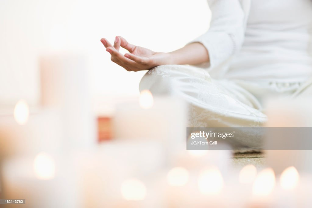 Hispanic woman meditating in lotus position near lit candles