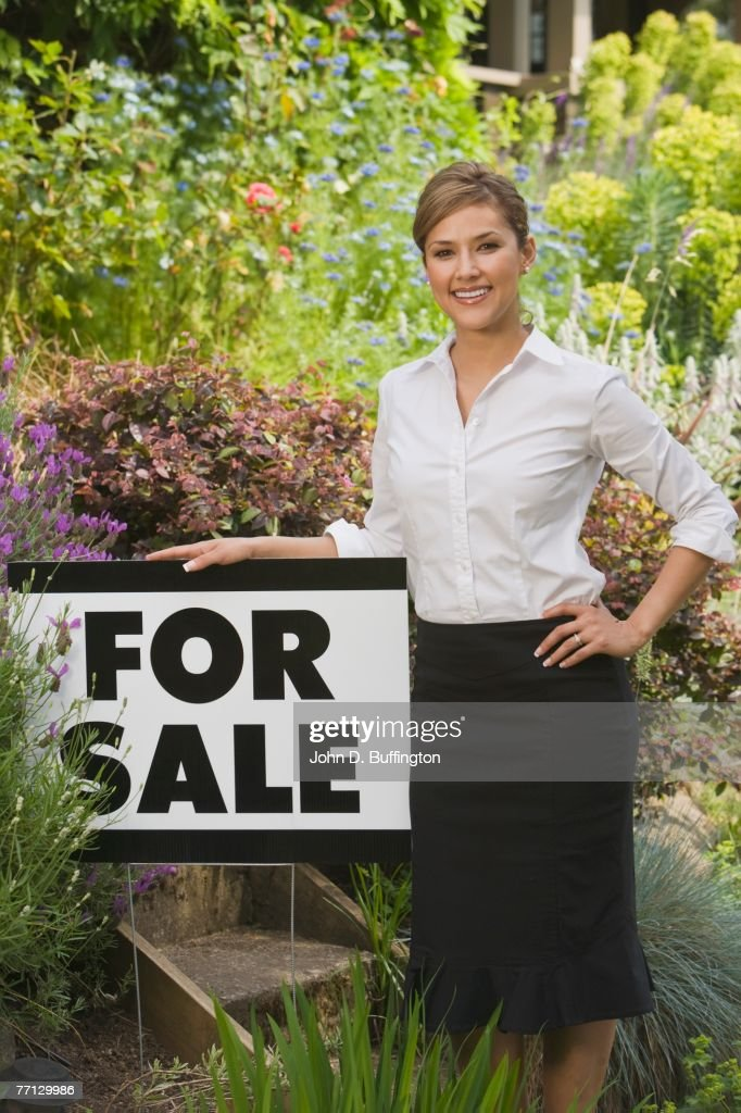 Hispanic woman next to For Sale sign : Stock Photo