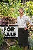 Hispanic woman next to For Sale sign