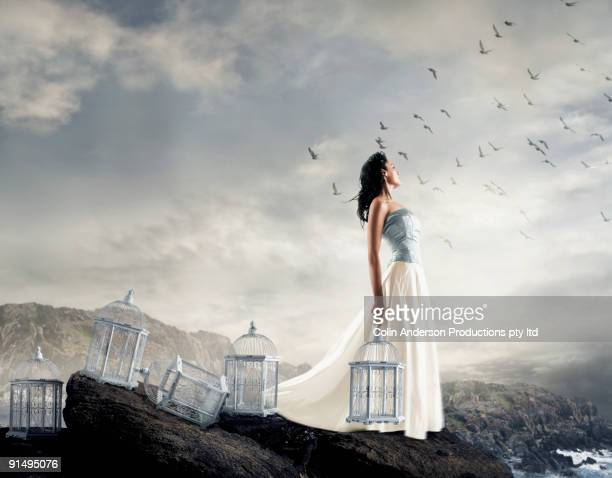 Hispanic woman on cliff with empty birdcages