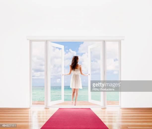 Hispanic woman opening French doors to ocean view