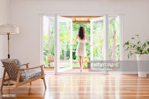 Hispanic woman opening French doors to patio