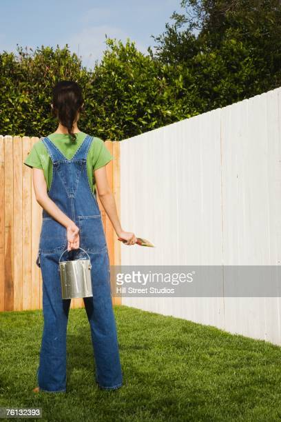 Hispanic woman painting fence