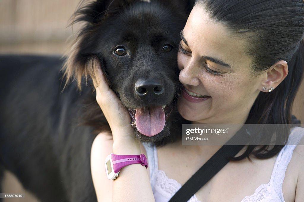 Hispanic woman petting dog : Stock Photo