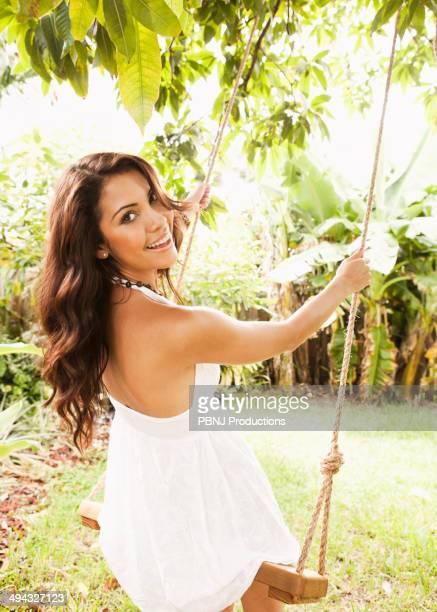 Hispanic woman playing on tree swing