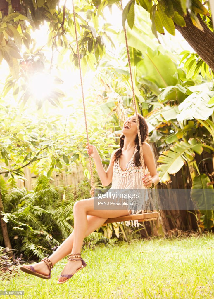 Hispanic woman playing on tree swing