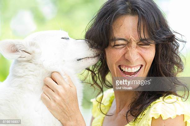 Hispanic woman playing with dog