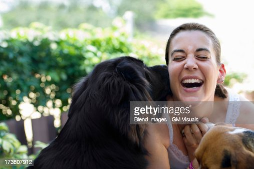 Hispanic woman playing with dogs : Stock Photo
