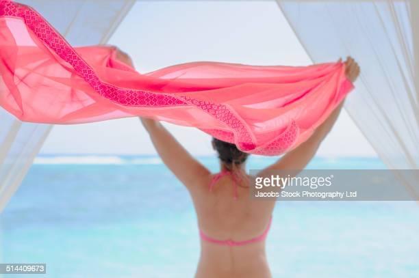 Hispanic woman playing with fabric on beach