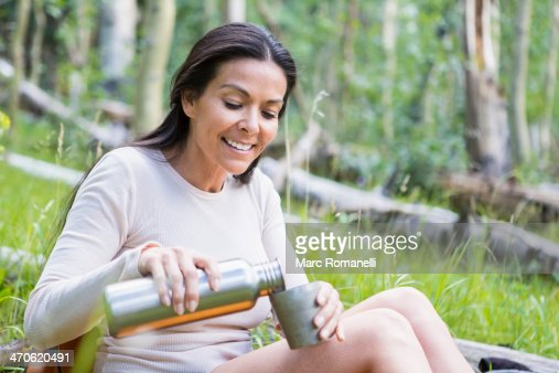 Hispanic woman pouring cup of coffee in forest