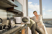 Hispanic woman pushing husband's head in microwave