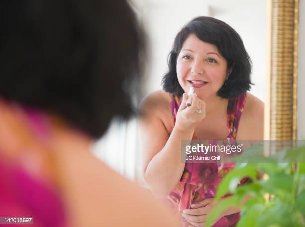 Hispanic woman putting on lipstick