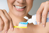 Hispanic woman putting toothpaste on toothbrush