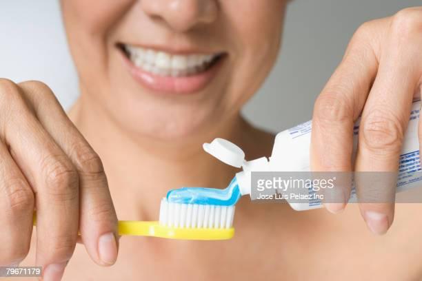 Hispanic woman putting toothpaste on toothbrush