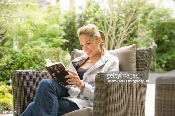 Hispanic woman reading book outdoors