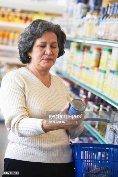 Hispanic woman reading label of can in grocery store