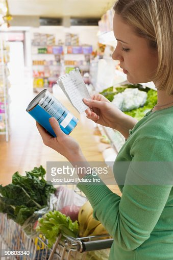 Hispanic woman reading label of canned food in grocery store : Stock Photo