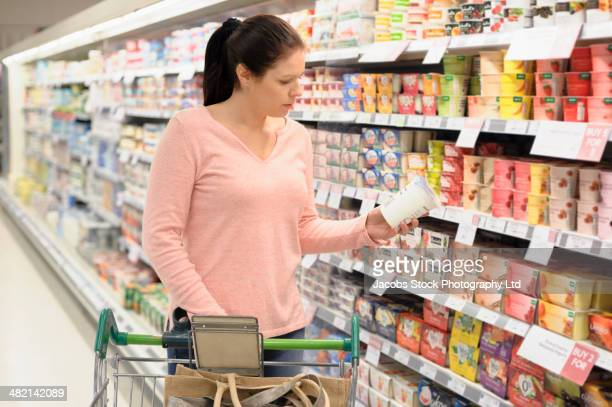 Hispanic woman reading label on container in supermarket
