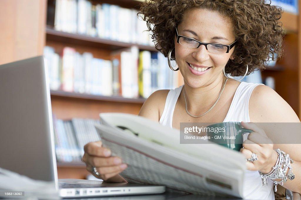 Hispanic woman reading newspaper in library : Stock Photo