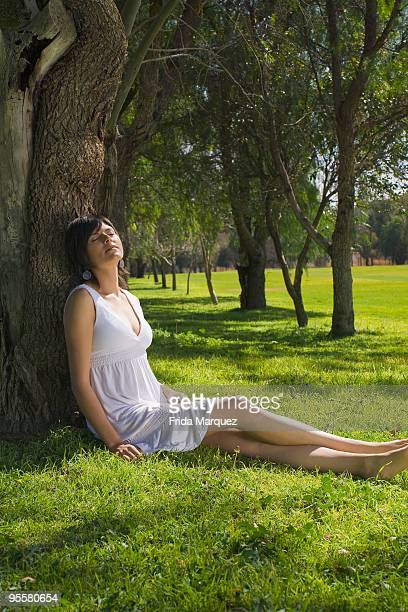 Hispanic woman relaxing against tree in park
