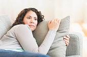 Hispanic woman relaxing on sofa