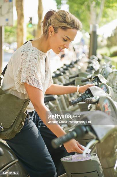 Hispanic woman renting bicycle