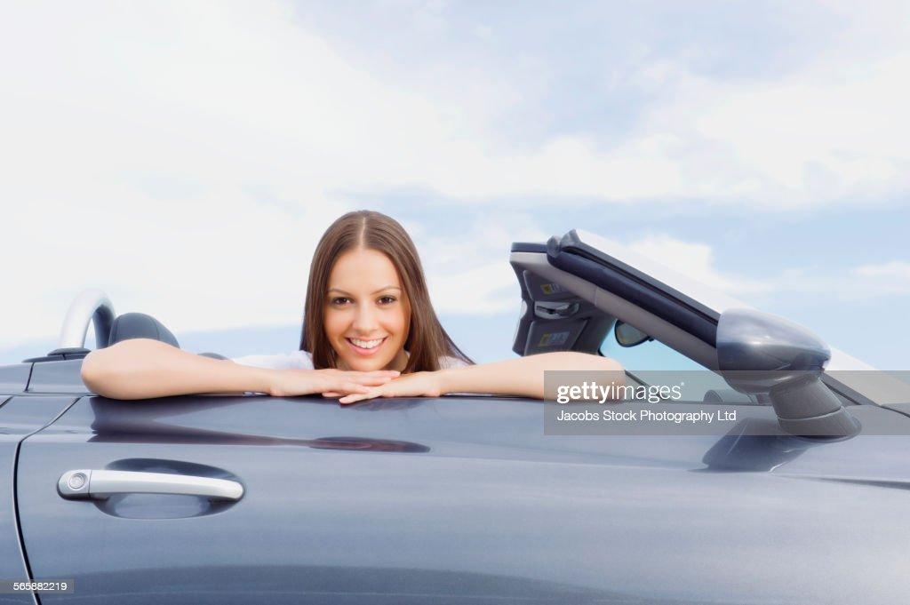 Hispanic woman resting chin on convertible door