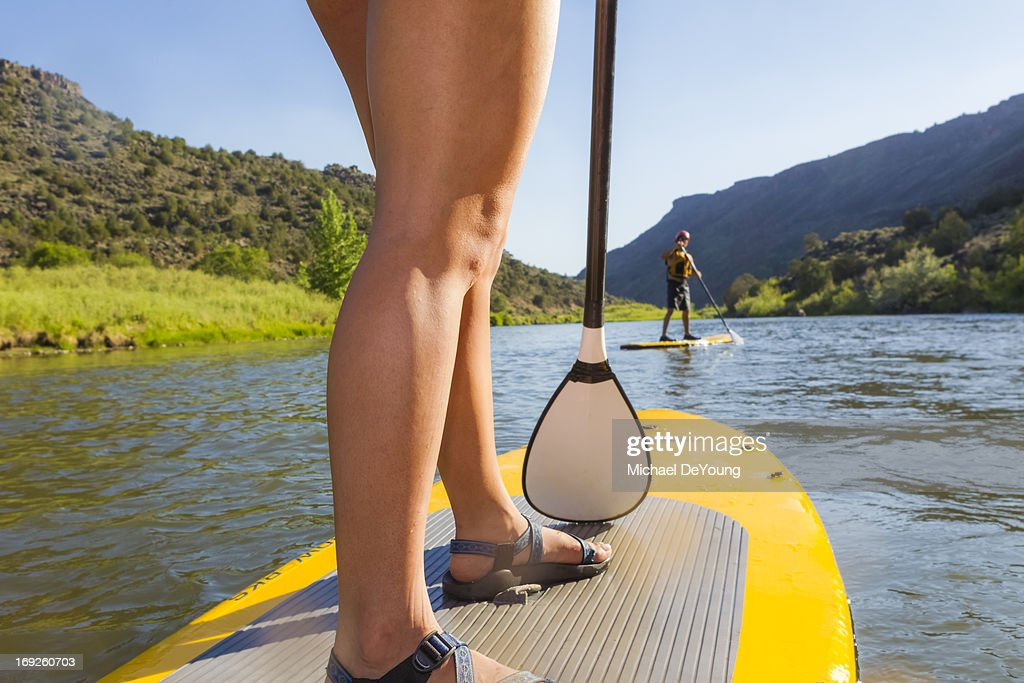 Hispanic woman riding paddle board