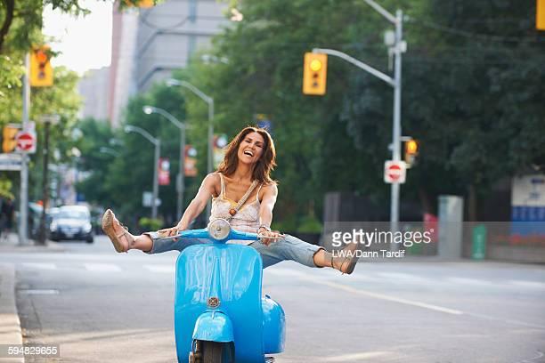 Hispanic woman riding scooter