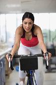 Hispanic woman riding stationary bicycle