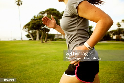 Hispanic woman running in park field : Stock Photo