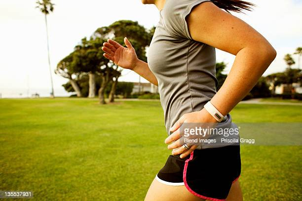 Hispanic woman running in park field