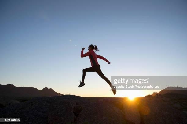 Hispanic woman running in rocky area